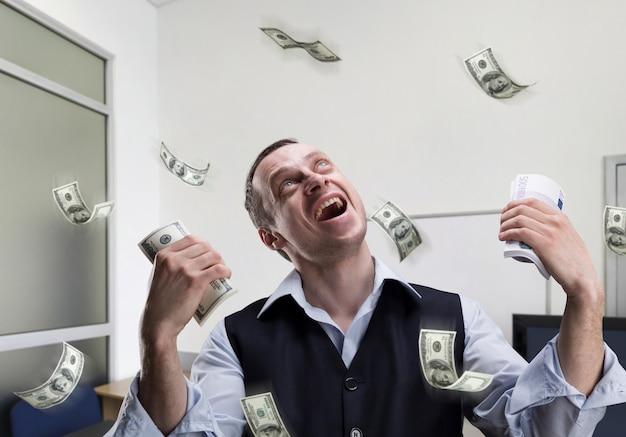 Счастливый бизнесмен держит деньги и мечтает в офисе