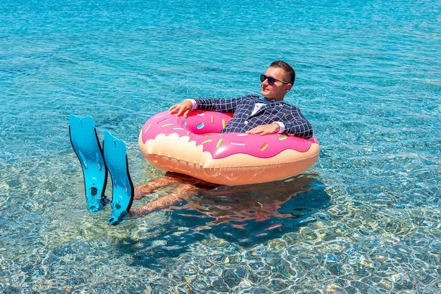 海で膨脹可能なドーナツの足ひれで幸せなビジネスマン