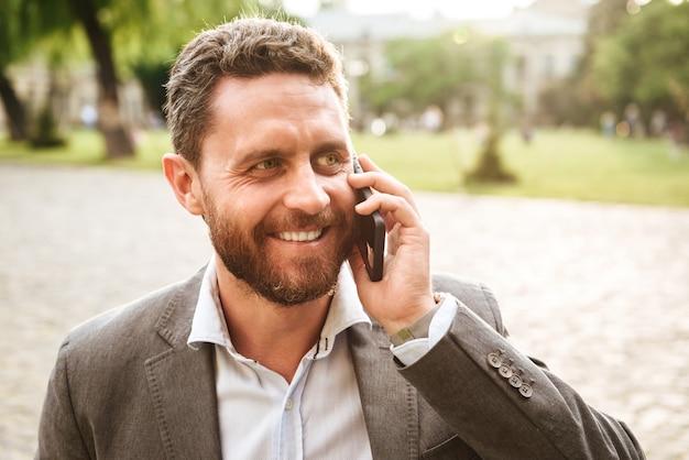 화창한 날에 공원에서 산책하는 동안 스마트 폰에 말하기 회색 클래식 정장에 행복 한 사업가