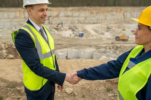 Счастливый бизнесмен в каске, пожимая руку женщины-строителя