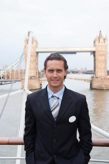 ロンドン、イギリスの幸せな実業家。男はタワーブリッジで微笑む。観光客は街の観光を楽しんでいます。ビジネスと娯楽のための旅行。アーキテクチャとデザインコンセプト。