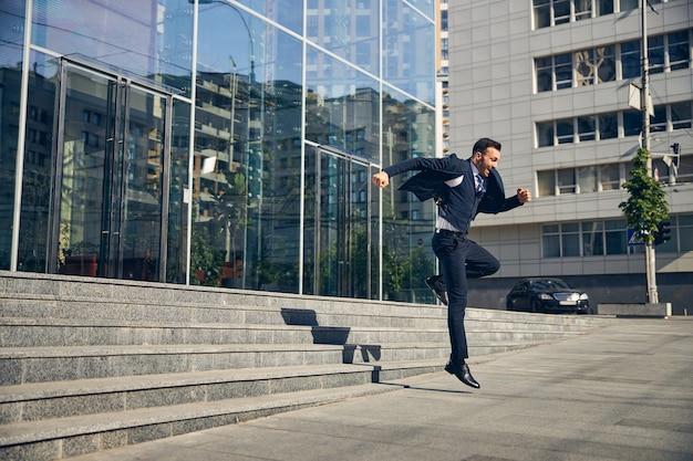 幸せなビジネスマンがビジネス センターの近くで喜びに飛び上がり、外を急いでいる