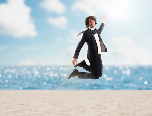 Счастливый бизнесмен прыгает на пляже