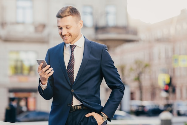 Happy businessman keeps hand in pocket wearing formal suit and wristwatch and using smart phone