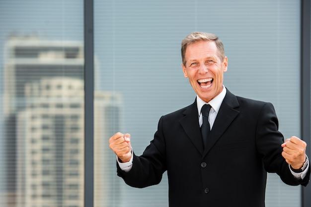 Happy businessman looking at camera near building