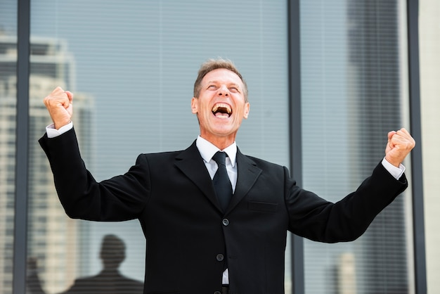 Happy businessman looking up near building