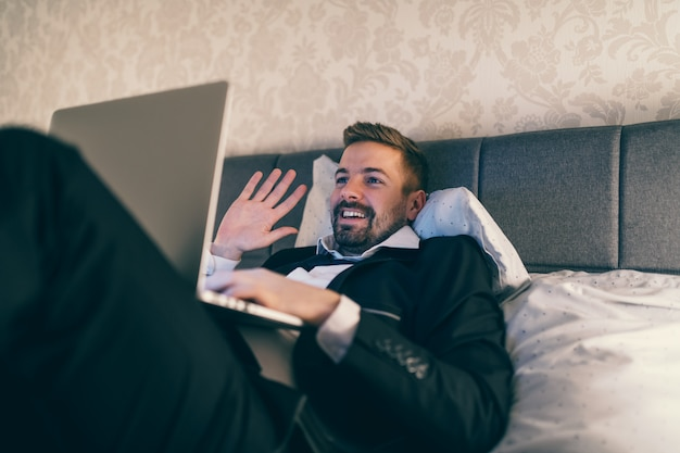 Happy businessman lying on the bed in hotel room in suit and using laptop for video call.