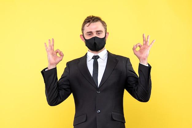 L'uomo d'affari felice fa il doppio segno giusto della mano su giallo