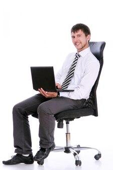 Счастливый бизнесмен на стуле с ноутбуком