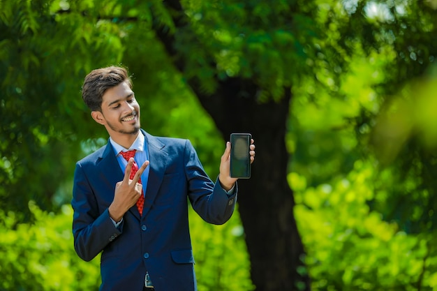 Happy businessman pointing finger on blank smartphone screen