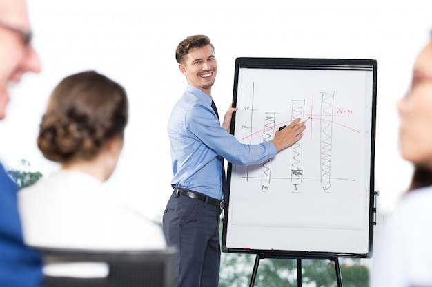 Happy businessman presenting bar chart to colleagues
