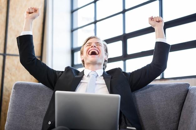 노트북 앞에서 흥분으로 손을 올리는 행복 한 사업가