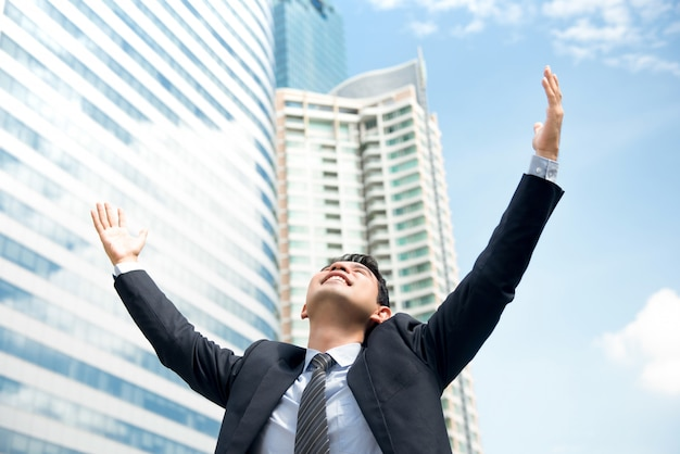 Happy businessman raising his arms in the air empowering himself