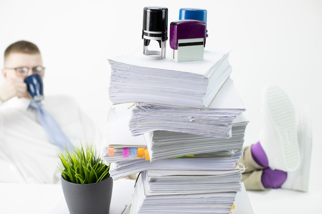 Happy businessman relax on coffee break with his legs on table with paperwork