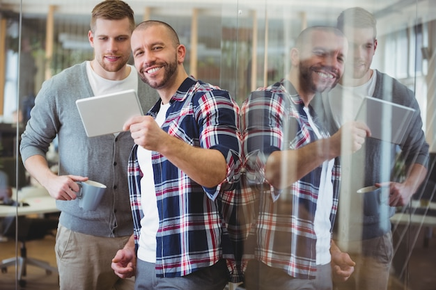 Happy businessman showing digital tablet to colleague