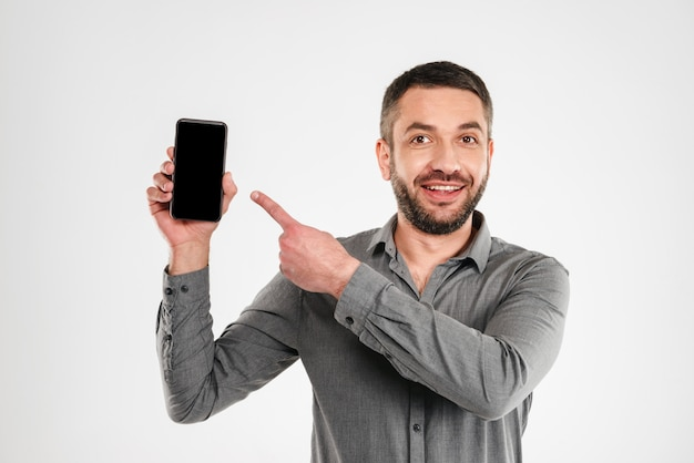 Happy businessman showing display of by mobile phone