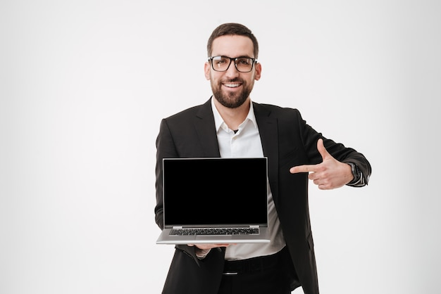 Happy businessman showing display of laptop computer and pointing.
