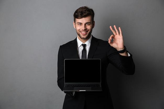 노트북 컴퓨터의 디스플레이 보여주는 행복 한 사업가