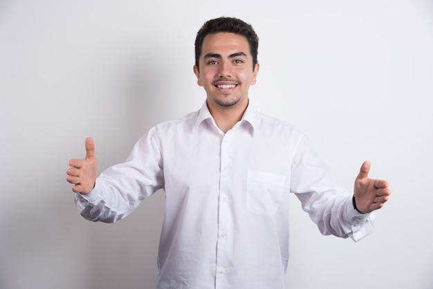 흰색 바탕에 그의 손을 보여주는 행복 한 사업가.