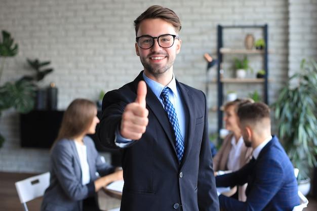 Счастливый бизнесмен показывает палец вверх с коллегами на заднем плане в офисе.