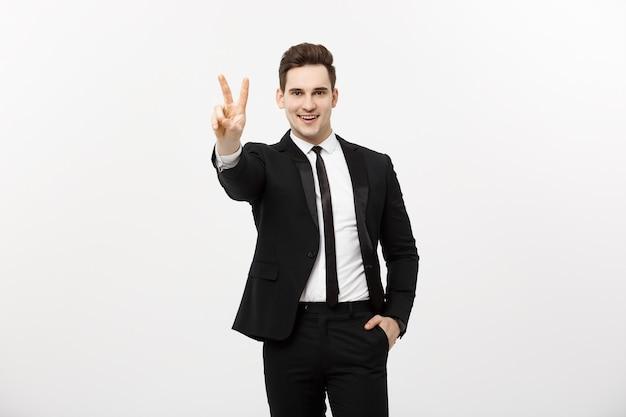 회색 배경에 대해 두 손가락이나 승리 제스처를 보여주는 행복한 사업가. 비즈니스, 직업 및 교육 개념의 성공. 광고, 슬로건 또는 텍스트를 위한 빈 카피스페이스 영역