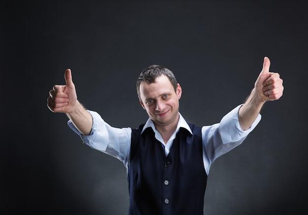 Счастливый бизнесмен показывает палец вверх над серым