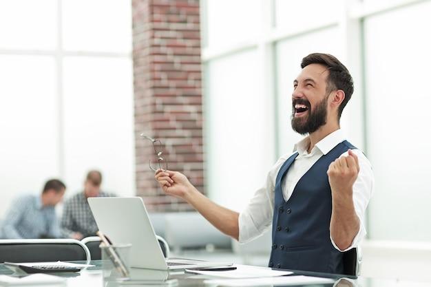 Счастливый бизнесмен, сидя за офисным столом