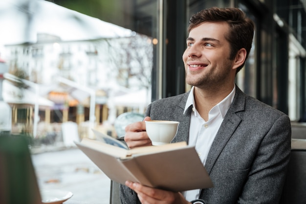 Happy businessman sitting by the table in cafe with laptop computer and looking away while holding book and cup of coffee