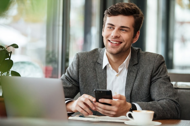 Happy businessman sitting by the table in cafe with laptop computer and smartphone while looking away