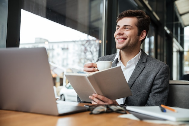 Happy businessman sitting by the table in cafe with laptop computer while reading book and drinking coffee