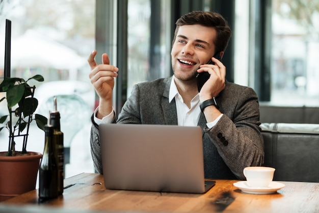 Happy businessman sitting by the table in cafe with laptop computer while talking by smartphone