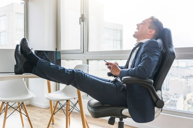 Happy businessman sitting on chair at workplace using mobile