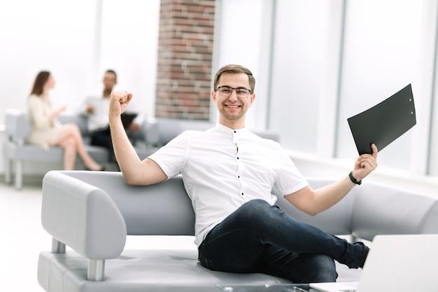 은행 로비에 앉아 있는 행복한 사업가. 비즈니스 개념