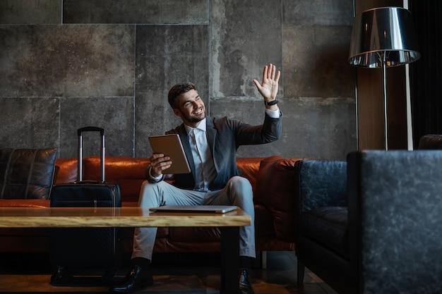 ホテルのホールで彼の荷物の横にあるソファに座って、タブレットを持って幸せなビジネスマン。彼は手を振っています。出張、シンポジウム、旅行