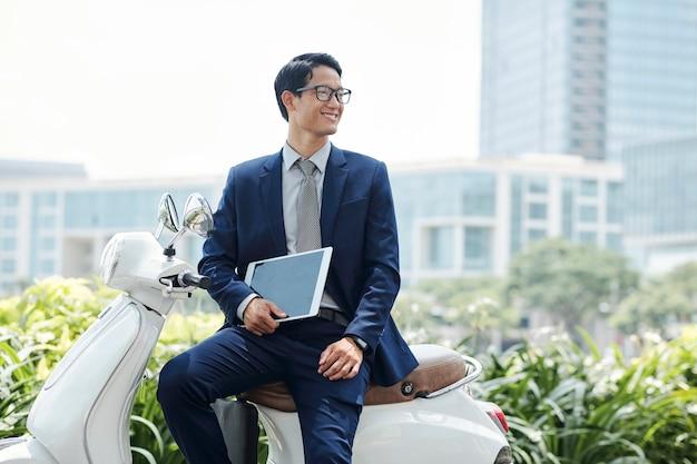 スクーターに座って幸せなビジネスマン