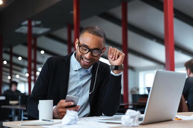 Счастливый бизнесмен улыбается и текстовых сообщений на смартфоне за столом