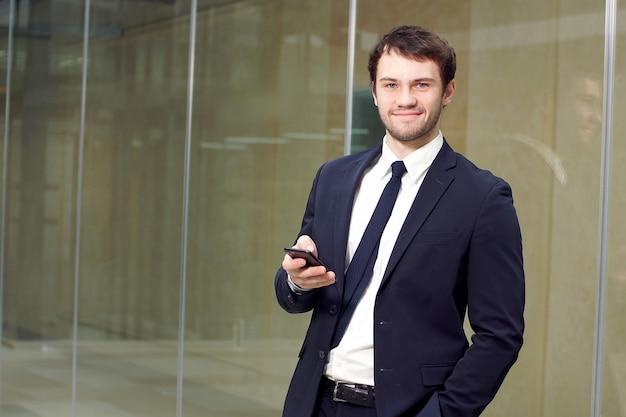 スマートフォンの手でオフィスのインテリアに立って、笑顔でカメラ目線の幸せなビジネスマン