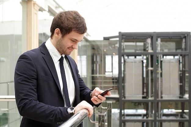手でスマートフォンでオフィスのインテリアに立って幸せなビジネスマン