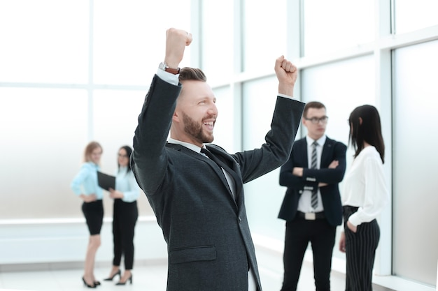 Счастливый бизнесмен, стоя в зале бизнес-центра