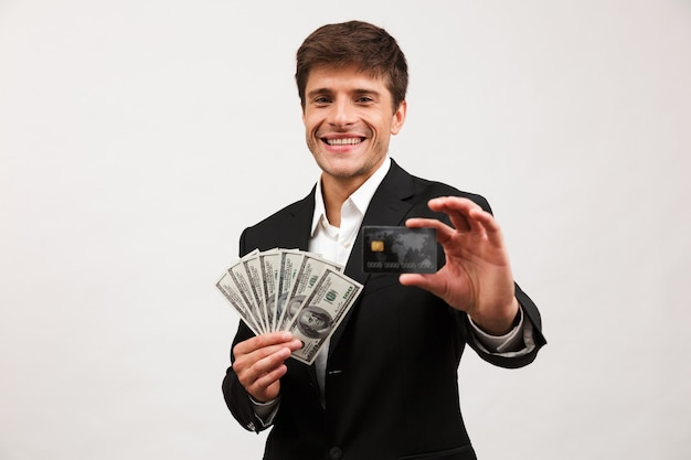 Happy businessman standing isolated holding money and credit card.