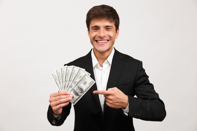 Happy businessman standing isolated holding money pointing.