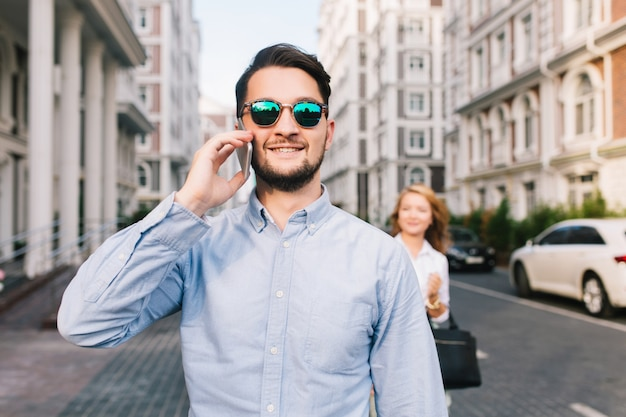 Happy businessman in sunglasses speaking on phone on street. pretty blonde girl catching him from behind