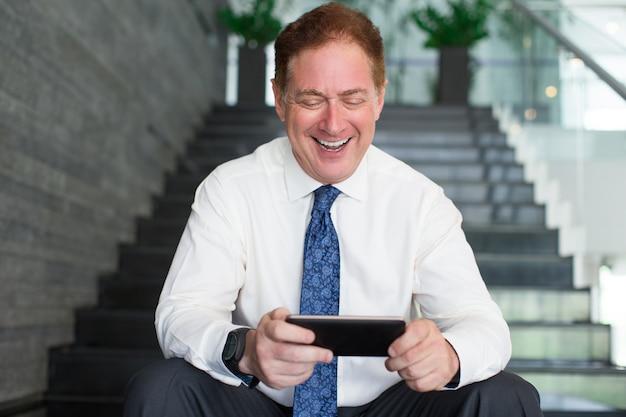 Happy businessman surfing internet on smartphone