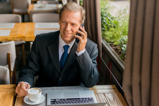 Happy businessman talking on mobile phone with cup of coffee and laptop on table