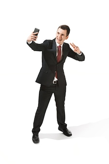 スタジオ撮影で白い背景の上に電話で話している幸せな実業家。立って自分撮り写真を作るスーツ姿の若い男を笑顔。