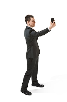 スタジオ撮影で白い背景に分離された電話で話している幸せなビジネスマン