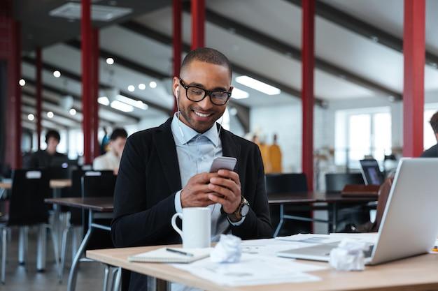 Счастливый бизнесмен текстовых сообщений на смартфоне в офисе