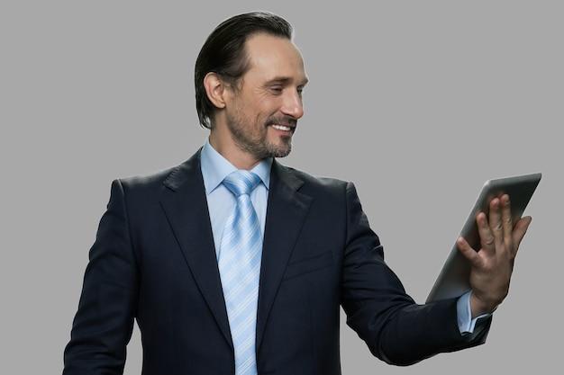 デジタルタブレットを使用して幸せなビジネスマン。休憩中に家族とビデオチャットをしている白人実業家の笑顔。テクノロジー、オンラインコミュニケーション、インターネット、そして人々のコンセプト。