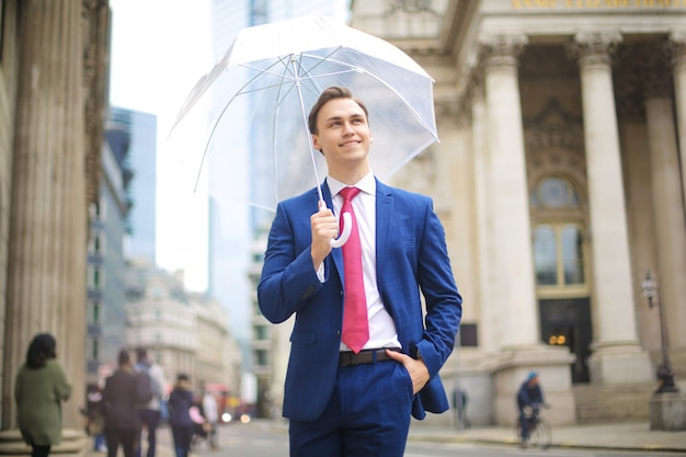 Happy businessman walking in the street, under the rain