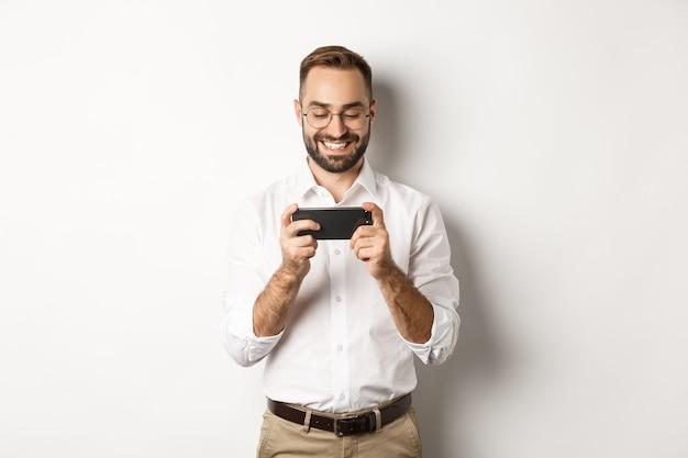 Happy businessman guardare video sul cellulare, in piedi.